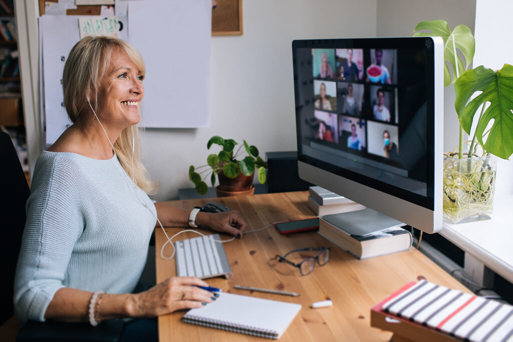 Smiling mature woman having video call via computer in the home